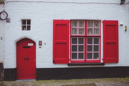 window shade: white and black facade of building from bricks with a red door and a large window with red shutters