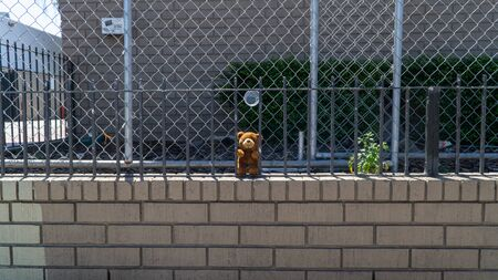 San Francisco, USA - August 2019: A Lonely brown teddy bear behind bars Stock Photo