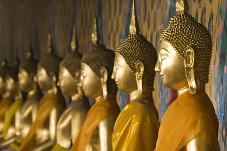 enlightening: Row of seated Buddhas at the temple of Wat Arun in Bangkok, Thailand.  Shallow focus on right Buddha.