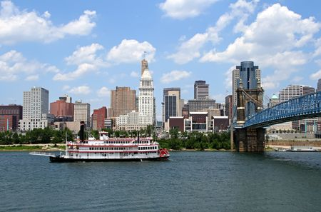 Replica steamboat travels down the Ohio River in front of the Cincinnati skyline.