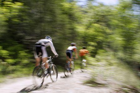 パン、森の中に乗って 3 つの山のバイカーのショットぼやけています。