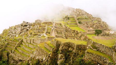 The Lost Incan City of Machu Picchu under heavy fog near Cusco, Peru.
