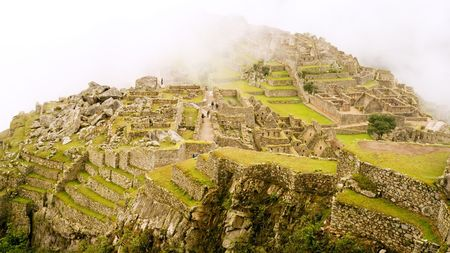 cusco: The Lost Incan City of Machu Picchu under heavy fog near Cusco, Peru.