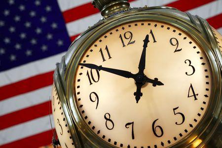 バック グラウンドでアメリカの国旗とグランド ・ セントラル駅の情報ブースの上にクロックします。