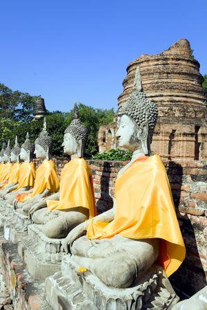 A row of Buddha statues at the temple of Wat Yai Chai Mongkol in Ayutthaya near Bangkok, Thailand.