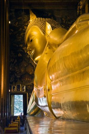 The reclining Buddha at Wat Pho in Bangkok, Thailand.   Largest reclining Buddha in the world. photo