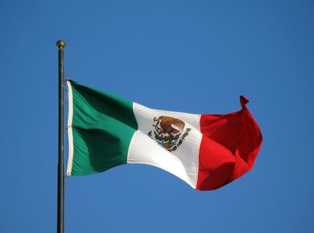 flagpole: Flagpole with The Flag of Mexico blowing in the wind against a blue sky background.