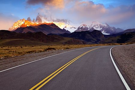 fitz roy: Curving road in Patagonia with sunrise illuminated Monte Fitz Roy near El Chalten, Argentina.