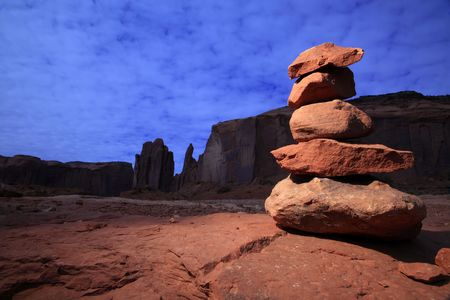 Dramatically lit zen-like tower of stones in Monument Valley. photo