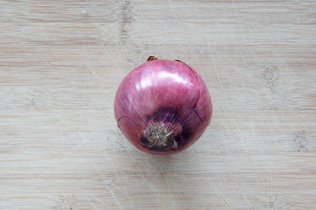 A solo red onion on top of a cutting board