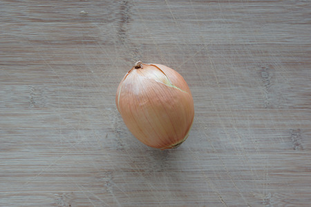 A solo white onion on top of a cutting board