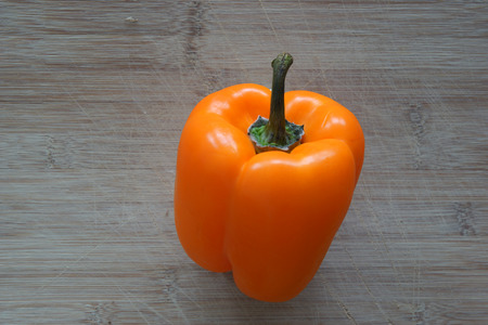 An orange bell pepper on top of a cutting board