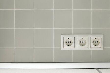 Drie witte elektrische op een witte muur tegels