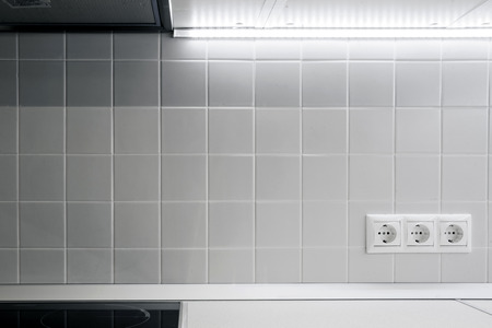 electric socket: Three white electric socket on the white wall tiles in the kitchen with white backlight