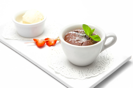 chocolate fondant in a white cup with strawberries decorated with mint