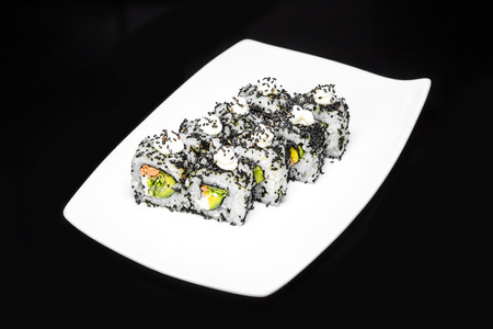 roll out: Sushi rolls set with crab meat and avocado sprinkled with black sesame seeds on a black background