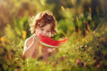 Two flying little boy eating watermelon in the meadow