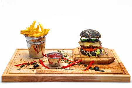 sesame street: Black cheeseburger with French fries in a bucket, ketchup on a wooden board Stock Photo