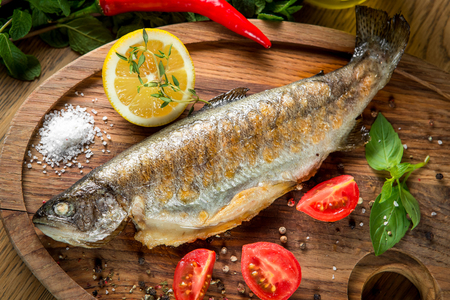coliflor: Fish dorado on grill with boiled cauliflower, lemon and tomatoes on a wooden board
