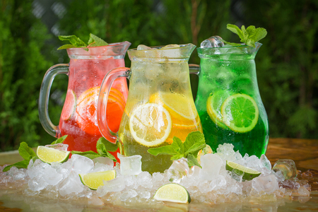 Three summer cocktails in ice with berries on a wooden table and green background