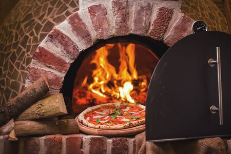 Taking tasty pizza out of oven in restaurant kitchen Archivio Fotografico