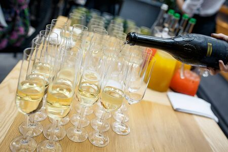 Sparkling wine is poured into a glass at a party Standard-Bild
