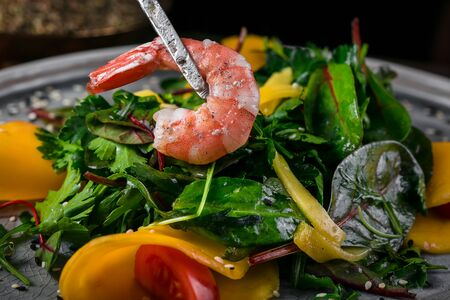 shrimp put in a salad of spinach arugula tomato and avocado Stock Photo