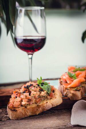 verschiedene Bruschetta auf einem Holzbrett mit einem Glas Wein