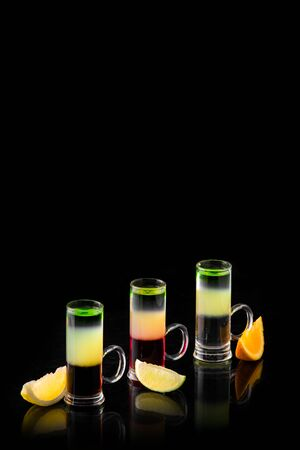 three different alcoholic cocktails with only orange and lemon on a black background isolated