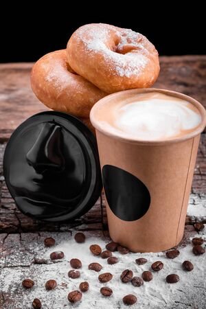 donuts sprinkled with powdered sugar next to a glass of coffee and coffee beans on a wooden table on a black background