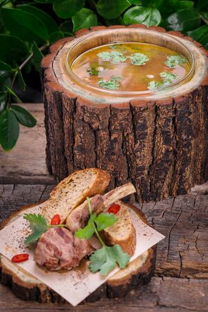 national traditional Ukrainian dish borsch with grilled lamb on a wooden board
