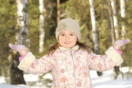 The little girl in winter clothes has lifted upwards hands and smiles Stock Photo - 4563913