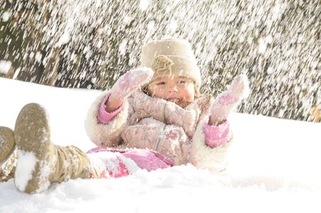 The little girl lays on a snow, on her throw a snow in the winter Stock Photo - 4563915