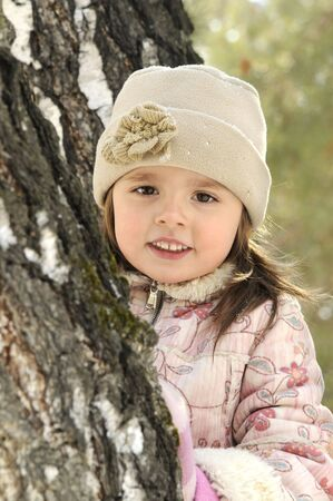 The little girl  near to a tree in the winter close up Stock Photo - 4563912