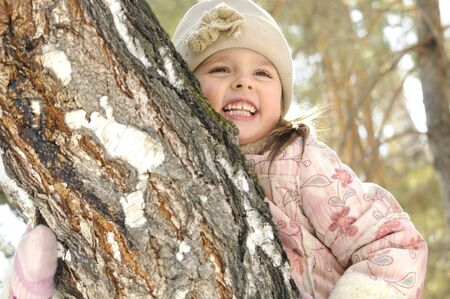 The little girl embraces a tree in the winter Stock Photo - 4563917