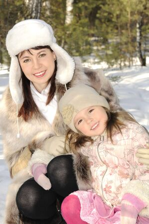 Mum together with the daughter embrace in the winter on the nature Stock Photo - 4563921