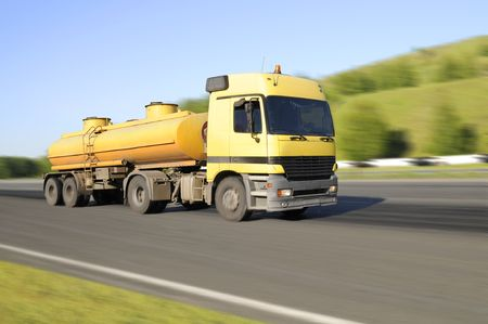 quickly: The  lorry, Yellow,  quickly rushes on highway, on a background of the beautiful nature Stock Photo
