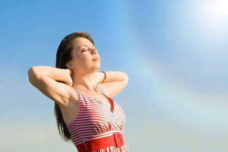 irradiation: The young beautiful girl sunburn under a solar stream of light on a background of the sky