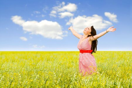 lifted hands: The young women  in a field with yellow colors, has lifted hands upwards, eyes are closed, smiles