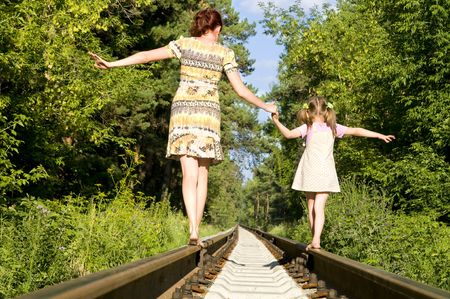 cross ties: Mother with the daughter go on rails, a back to a camera, in a wood, in the summer Stock Photo