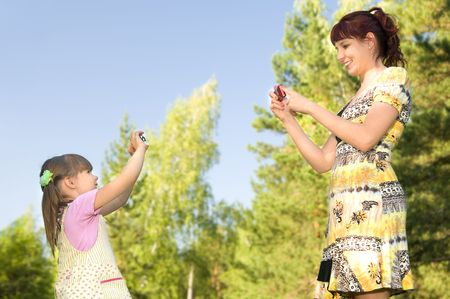 Mother together with a daughter each other on the digital device,  outdoor . photo