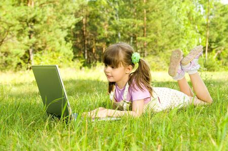 The small nice girl works on a computer, lays on a beautiful green lawn, Smile photo