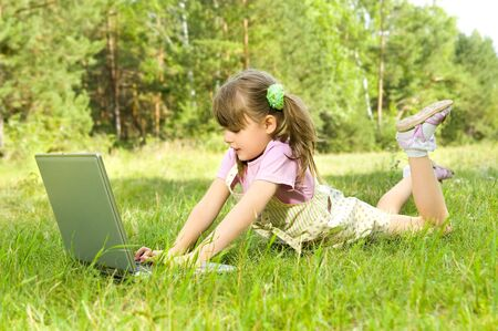 lays: The small nice girl works on a computer, lays on a beautiful green lawn, Smile