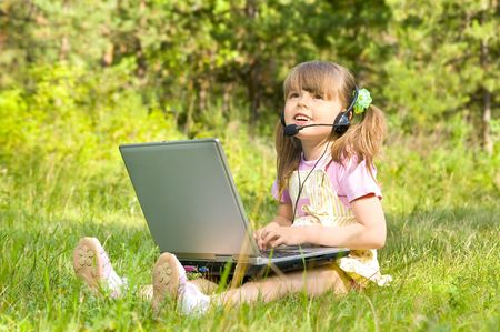 communicates: The small nice girl works on a computer, lays on a beautiful green lawn, Smile