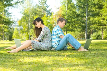 Young beautiful guy and the girl, sits on a lawn, have a good time about with laptop.  Adobe RGB (1998) photo