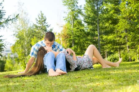 female sexuality: Young beautiful guy and the girl, sits on a lawn, kisses .  Adobe RGB (1998) Stock Photo