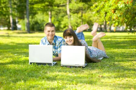 Young beautiful guy and the girl, lay on a lawn, have a good time about with laptop.  Adobe RGB (1998) photo