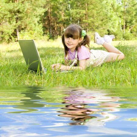 lays: The small nice girl works on a computer, lays on a beautiful green lawn, Smile .