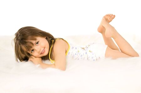 underwear: Beautiful, small the girl lays a stomach downwards on white to fur, smiles Stock Photo