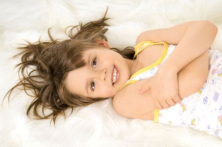 girls underwear: Beautiful, small the girl lays a stomach downwards on white to fur, smiles Stock Photo